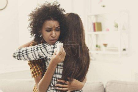 Photo pour Femme embrassant son ami déprimé à la maison, gros plan. Jeune fille soutenant sa petite amie qui pleure. Amitié consolation et soins, espace de copie - image libre de droit