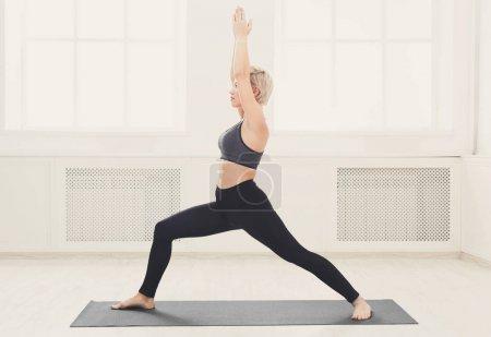 Photo pour Fitness femme warm-up qui s'étend de formation à fond blanc à l'intérieur. Jeune mince jeune fille fait d'exercice d'aérobic, espace copie - image libre de droit