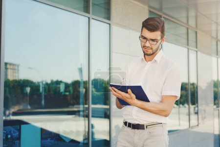 Photo for Attractive pensive businessman in eyeglasses making notes in notepad while standing near an office building, copy space. Man in formalwear noting his ideas. Business and success concept - Royalty Free Image