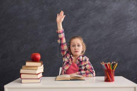 Photo pour Portrait de mignonne fille intelligente levé la main tout en étant assis avec pile de livres à table, espace de copie. Concept d'éducation et de développement - image libre de droit