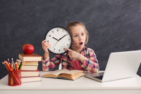 Photo for Portrait of cute smart girl sitting with stack of books and laptop, holding big clock and pointing on it. Education, development, time management, deadline, time to study, school concept - Royalty Free Image
