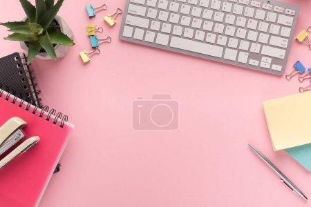 Photo pour Bureau avec cactus, clavier, bloc-notes et papeterie sur fond rose, espace de copie, vue de dessus. Lieu de travail féminin, concept de style de vie - image libre de droit