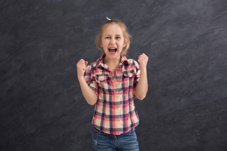 Photo for Little girl screaming at dark studio background. Desperate child yelling, emotional stress concept - Royalty Free Image