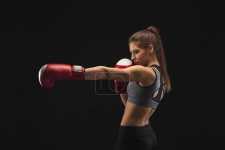 Photo for Side view of a gorgeous young woman with boxing gloves, standing in position, ready to fight, copy space. Studio shot on black background, low key. Kickboxing and fight sport concept - Royalty Free Image