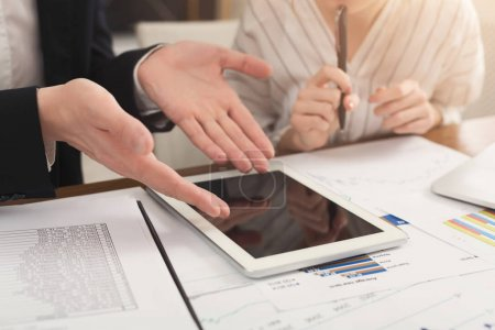 Photo for Closeup of business partners hands using digital tablet with blank screen for advertisement and having troubles. Financial background, count and pay an account, copy space - Royalty Free Image