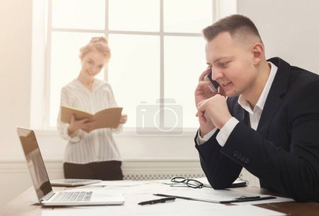 Photo for Business partners working at office. Serious and tired managers developing marketing strategy at modern workplace with laptop and papers, copy space, selective focus - Royalty Free Image