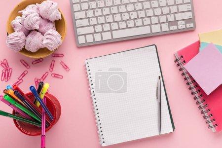 Photo pour Bloc-notes de spirale comme la maquette pour votre conception sur fond rose avec clavier, guimauves en plaque et papeterie, vue de dessus. Jeune fille au travail, concept lifestyle avec espace copie - image libre de droit
