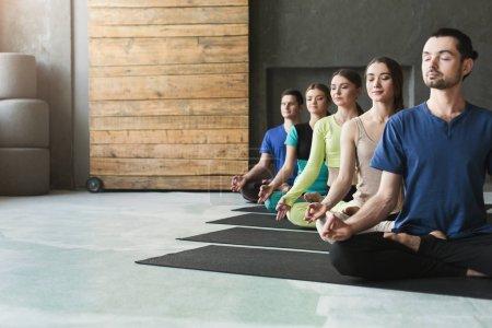 Photo pour Jeunes femmes et hommes en cours de yoga, exercices de méditation. Lotus pose pour la détente. Style de vie sain dans le club de fitness, culture, espace de copie - image libre de droit
