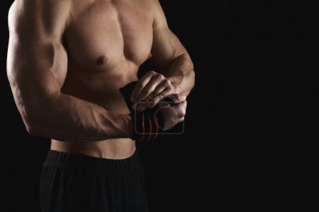 Photo for Strong athletic boxer wrapping hands with boxing tape before fight. Handsome male fitness model with naked torso and muscular body at black studio background, low key. Bodybuilding concept, copy space - Royalty Free Image