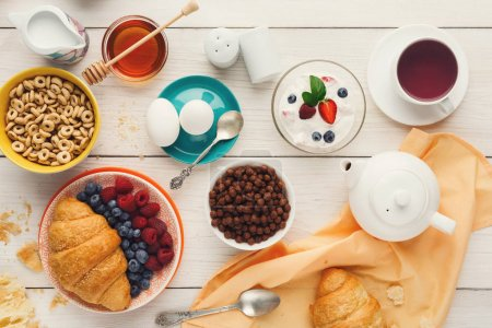 Photo for Rich breakfast menu background. French crusty croissants, muesli, yogurt, coffee, berries, honey and boiled eggs for tasty morning meals on wooden table, top view - Royalty Free Image