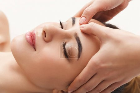 Photo for Woman enjoying anti aging facial massage. Pretty girl getting professional skin care at wellness center. Relaxation, beauty, spa and face treatment concept, copy space - Royalty Free Image