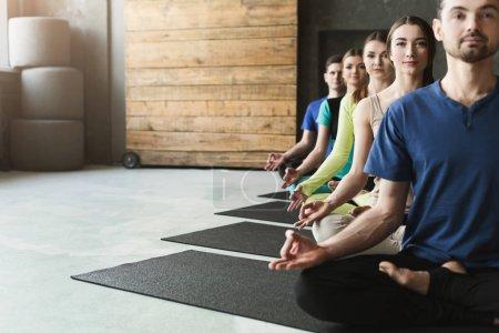 Photo pour Jeunes femmes et hommes en cours de yoga, exercices de méditation. Lotus pose pour la détente. Style de vie sain dans le club de fitness, culture, espace de copie, accent sélectif - image libre de droit