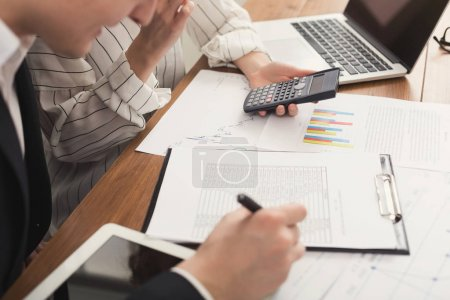 Photo for Closeup of business colleagues hands working with financial documents and counting account on calculator. Financial background, count and pay an account, copy space, selective focus - Royalty Free Image