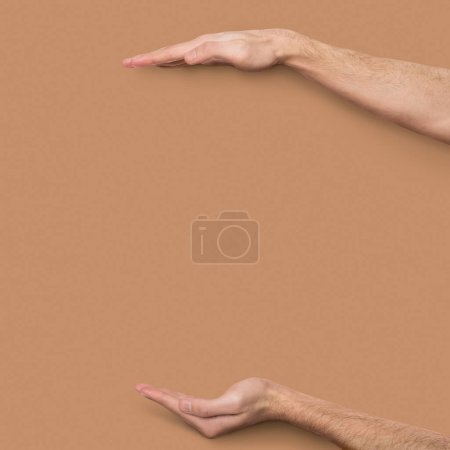 Male hands measuring invisible item at beige background