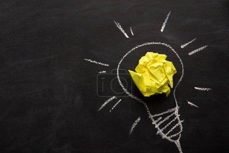 Photo pour Fond d'inspiration créative - ampoule comme métaphore de l'idée. Ampoule électrique dessinée sur tableau avec papier jaune froissé pour lueur. Concept d'innovation et de barainstorming, vue de dessus, espace de copie - image libre de droit