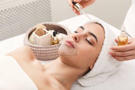 Photo pour Massage du visage. Spa, station balnéaire, concept beauté et santé. Belle femme recevant un traitement professionnel du visage avec de l'huile biologique nourrissante, espace de copie - image libre de droit