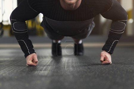 Photo pour Un jeune homme s'entraîne dans un club de fitness. Homme méconnaissable faisant des exercices de planche ou de push ups sur les poings, s'entraînant à l'intérieur, copiant l'espace - image libre de droit