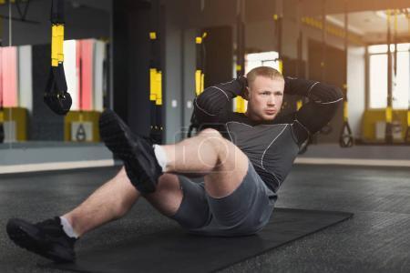 Photo pour Un jeune homme s'entraîne dans un club de fitness. Portrait d'un caucasien faisant de l'exercice, des redressements assis et des craquements pour les muscles abdominaux, s'entraînant à l'intérieur dans une salle de gym - image libre de droit