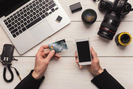 Photo pour Photographe achats en ligne avec carte de crédit et smartphone, assis sur le lieu de travail, commander du nouvel équipement photographique, espace de copie - image libre de droit