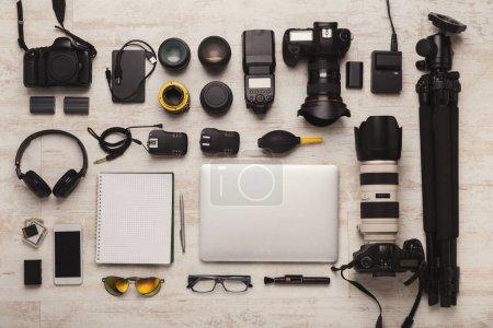 Foto de Conjunto de equipos fotográficos modernos en mesa de madera blanca, vista superior. Herramientas profesionales de diseñador creativo, fondo del lugar de trabajo del fotógrafo - Imagen libre de derechos