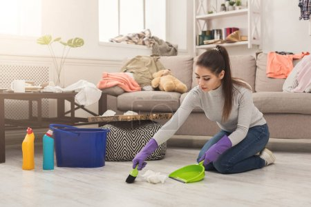 Photo for Young woman cleaning house, sweeping floor with broom and scoop in messy room, copy space - Royalty Free Image
