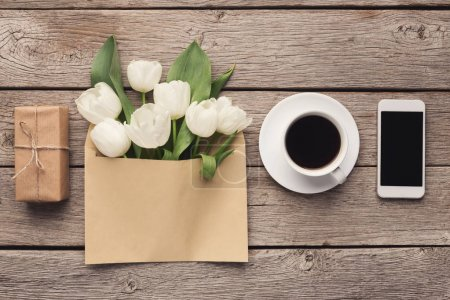 Photo for White tulips on wooden background. Creative bouqet in envelope, gift box, coffee, smartphone. Mothers Day, Women Day, floral desing, blogger table, online order concept, copy space, top view, flat lay - Royalty Free Image