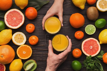 Photo for Hands of couple holding fresh juice glasses for breakfast on table with lots of assorted citrus fruits. Top view on oranges, lemons, tangerines and other exotic fruits, flat lay, copy space - Royalty Free Image