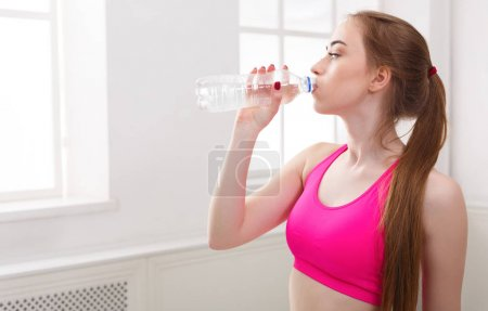 Photo for Young sport woman drinking water. Confident fitness girl holding plastic bottle, rest after training, healthy lifestyle concept, copy space - Royalty Free Image