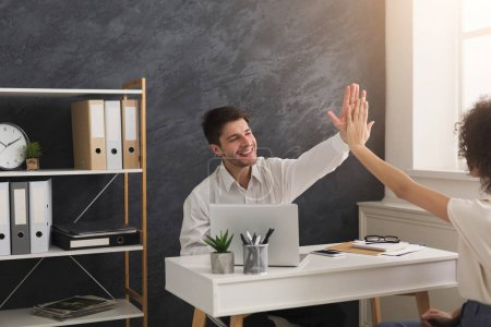 Photo for Winner business partners happy, successful, in white modern office, sitting at workplace. Colleagues giving high five, success concept - Royalty Free Image