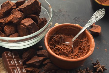 Photo for Chocolate background. Bowl and vintage spoon with cocoa powder, variety of candies and spices on black slate table, closeup. Sweet wallpaper, confectionery shop advertising and cooking ingredients - Royalty Free Image