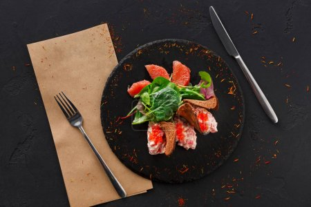 Photo for Gourmet seafood snack on black plate top view, copy space. Appetizing meal with red salmon, caviar and crispy toasts, restaurant serving - Royalty Free Image