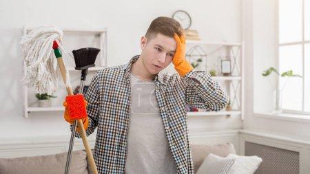 Photo pour Jeune homme fatigué balayant la maison, ayant mal à la tête. Concept d'entretien ménager, de nettoyage et de rangement des ressorts, espace de copie - image libre de droit