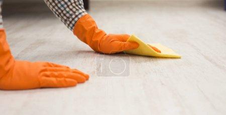 Photo pour Homme méconnaissable laver le sol en bois avec une serviette dans le salon. Entretien ménager, nettoyage et nettoyage concept de service, espace de copie - image libre de droit