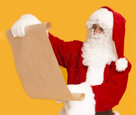 Photo for Father Christmas checking wishlist from children written on big cardboard paper, orange background - Royalty Free Image