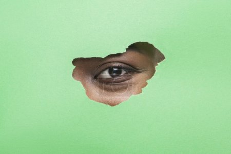 Photo for No Makeup. Black Female Eye Without Mascara Looking Through Torn Green Paper, Copy Space - Royalty Free Image