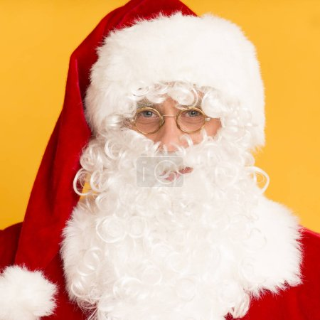 Photo for Merry Christmas. Cheerful Santa Claus face in glasses and red hat over orange background - Royalty Free Image