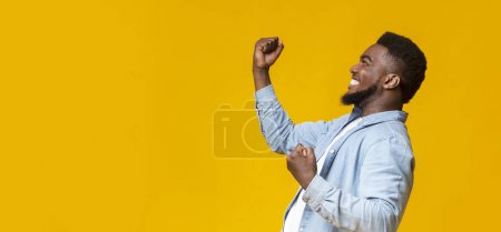 Foto de Hooray. Happy african American man raising fists in the air, celebrating success over yellow background with free space. - Imagen libre de derechos