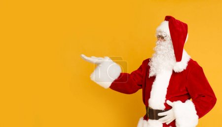 Photo for Merry Christmas original greeting. Santa Claus pointing at copy space for advertisement on orange background, panorama - Royalty Free Image