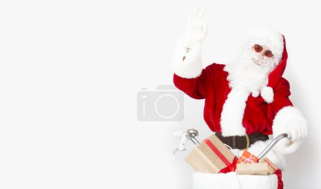 Photo for Merry Christmas. Happy Santa in sun glasses riding a bike with presents to warm countries, panorama, copy space - Royalty Free Image