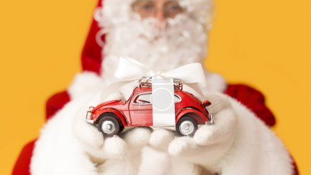 Photo for Christmas promo. Blurred Santa Claus suggesting toy car with present bow on orange background - Royalty Free Image