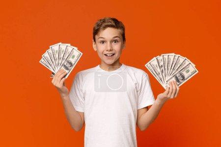 Photo pour Finance et épargne. Adolescent émotionnel tenant fans de dollars, fond de studio orange - image libre de droit
