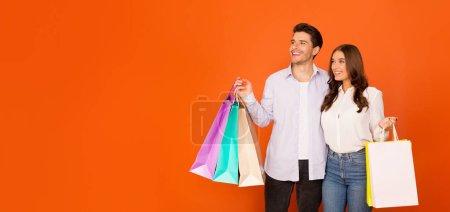 Photo pour Shopping saisonnier. Jeune couple avec des sacs à provisions colorés à la recherche d'espace libre, fond studio orange - image libre de droit