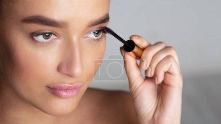 Photo pour Belle femme millénaire appliquant du mascara sur les cils avec une brosse sur fond gris - image libre de droit