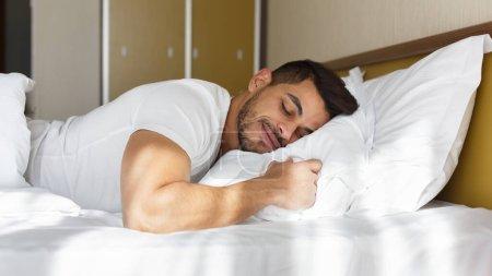 Photo pour Jeune homme oriental dormant paisiblement dans son lit, panorama avec espace de copie - image libre de droit