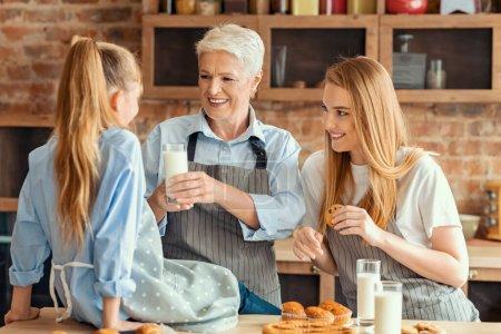 Photo pour Concept d'aliments et de boissons sains. Grand-mère joyeuse donnant un verre de lait à la petite fille, mère tenant des cookies, passant du temps à la cuisine ensemble - image libre de droit