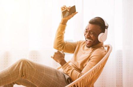 Photo pour App musicale. heureux noir homme dans sans fil casque en utilisant téléphone écoute playlist et chanter assis sur chaise intérieure . - image libre de droit