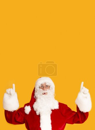 Photo for Creative Christmas card with Santa Claus indicating on copy space above on orange background - Royalty Free Image