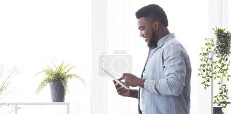 Photo pour Homme africain joyeux utilisant une tablette numérique tout en se tenant près de la fenêtre à la maison, vue latérale - image libre de droit