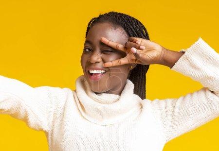Photo pour Fille d'hiver noire insouciante prenant selfie, couvrant l'œil avec un geste de paix, fond jaune - image libre de droit