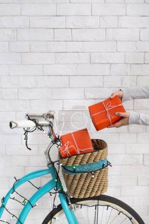 Photo pour Carte de Noël avec femme et cadeaux sur bicyclette rétro sur briques blanches mur, panorama vertical, espace copie - image libre de droit